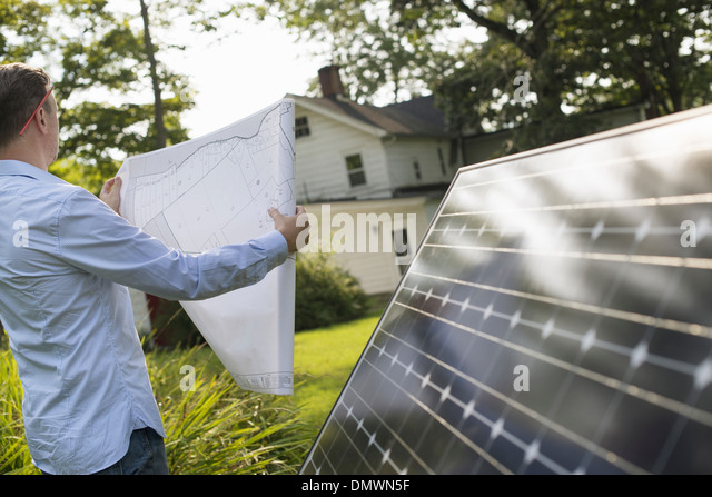 A man using a plan to place a solar panel in a farmhouse garden. - Stock Image