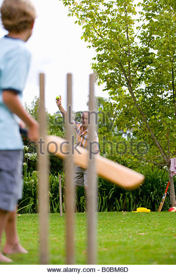 Boy 10-12 playing cricket with father, low angle view - Stock Image