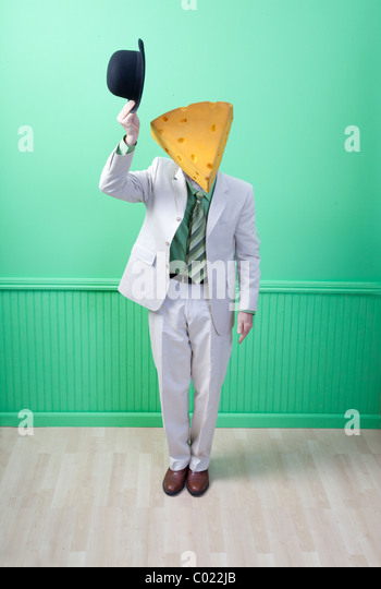 Man in suit wearing cheese head tipping hat - Stock Image