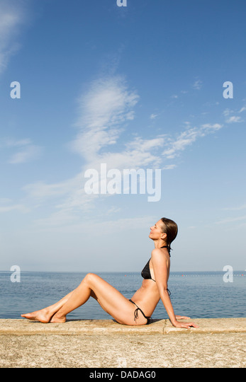 Woman sitting on wall by the sea - Stock Image