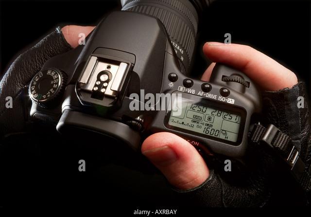 Hands holding a digital SLR camera - Stock Image