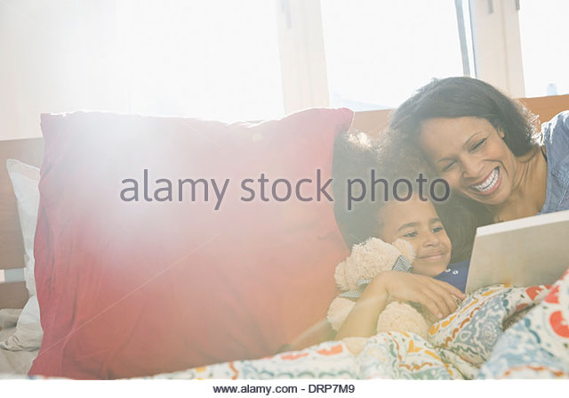 Mother reading story book to daughter - Stock Image