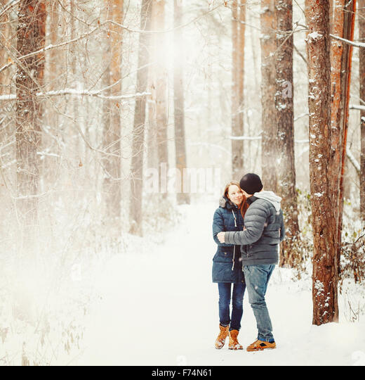 Young Couple Embracing in Winter Forest. Winter Vacations. Weekend Getaway. Space for Text. Natural Colors, Selective - Stock-Bilder
