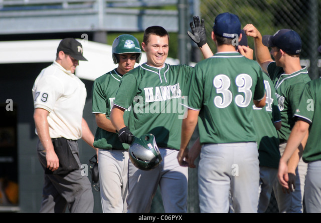 Player shows his pleasure as he celebrates with his teammates after hitting a home run during a high school baseball - Stock Image