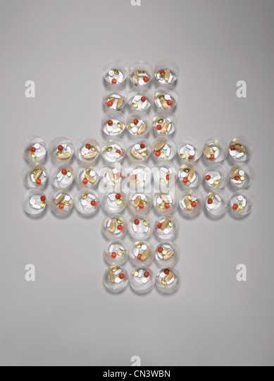 Pill containers arranged in cross shape - Stock Image