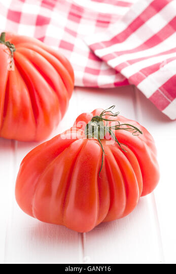 Coeur De Boeuf. Beefsteak tomatoes on white table. - Stock Image