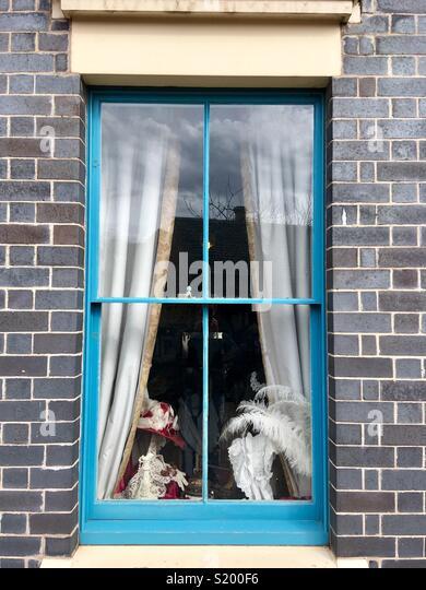 Blue sash window displaying hats - Stock Image