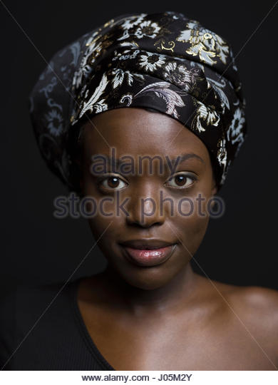 Close up portrait confident African American woman wearing headscarf against black background - Stock Image