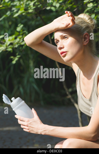 Young woman sitting outdoors with water bottle, wiping forehead with back of hand - Stock-Bilder