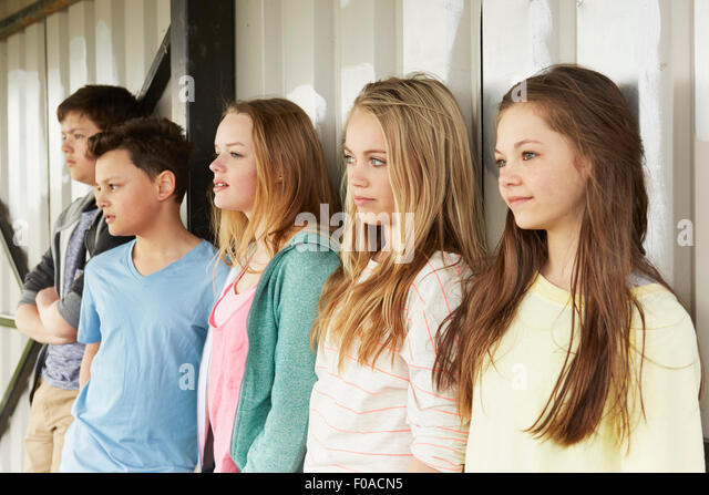 Row of five girls and boys looking out from shelter - Stock Image