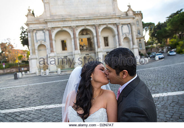 Newlyweds kissing at a roman water fountain - Stock-Bilder