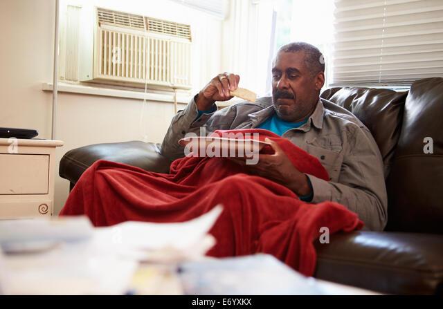 Senior Man With Poor Diet Keeping Warm Under Blanket - Stock Image
