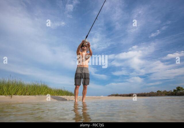 Low angle view of mature man fishing, Fort Walton, Florida, USA - Stock Image
