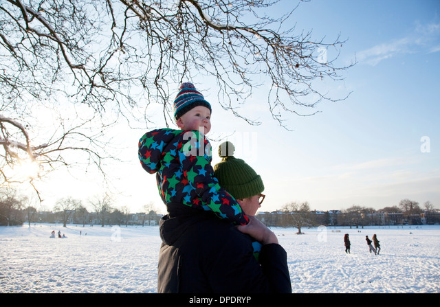 Father carrying child on shoulder in park - Stock Image
