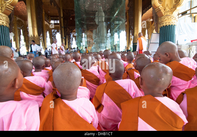A sea of balled heads. young Buddhist nuns in a religious gathering by the white marble Buddha at the Kyauk Daw - Stock-Bilder