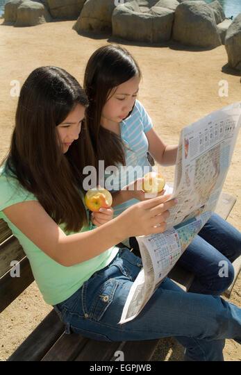 California Teens hanging out Mixed race Vietnamese/Caucasian and Hispanic/Caucasian girls read newspaper together - Stock-Bilder