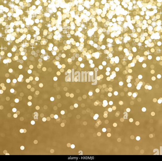 Glittery gold Christmas background with stars and bokeh lights - Stock Image