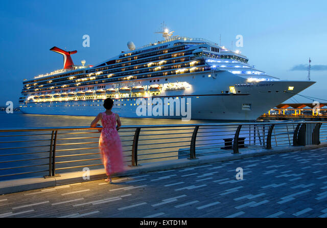 Woman admiring cruise ship from  Bahia Urbana (Urban Bay), Old San Juan, Puerto Rico - Stock Image