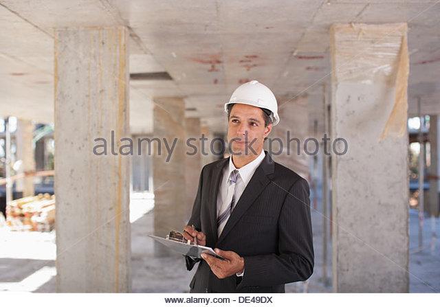 Businessman in hard-hat on construction site - Stock-Bilder