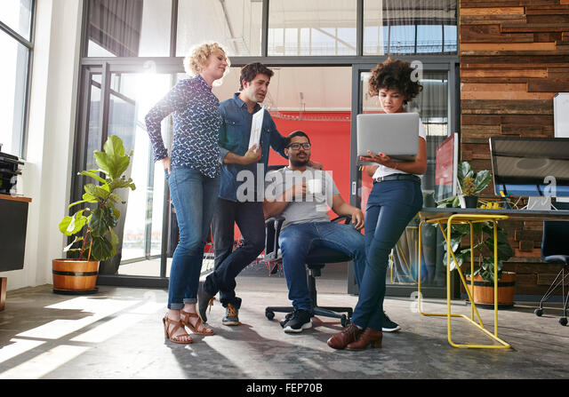 Multiracial group of designers meeting in modern office discussing work. Young entrepreneurs having a meeting for - Stock Image
