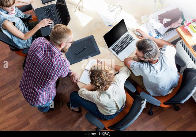 Overhead view design professionals working at laptops in meeting - Stock-Bilder
