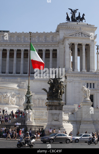 The Italian flag flies outside the national memorial to Vittorio Emanuele II in Rome, Italy. - Stock Image