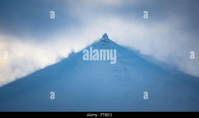Wind blowing snow off mountain peak in  Bolterdalen, near Longyearbyen, Spitsbergen Svalbard - Stock Image