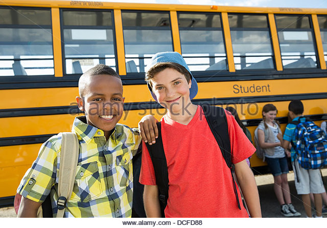 Portrait of schoolboys standing in front of bus - Stock Image