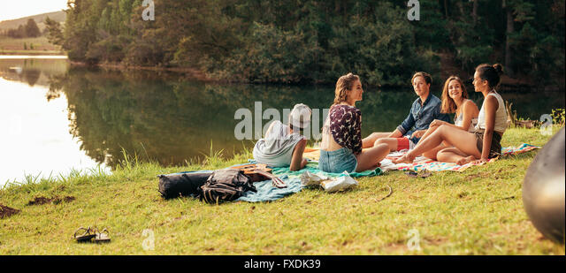 Young friends having picnic near a lake. Young friends enjoying a day at the lake. - Stock Image