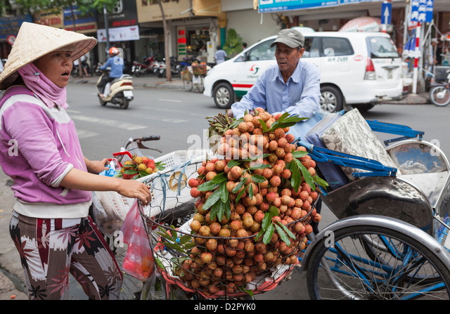 A cycle rickshaw driver stops to buy fruit from a lady outside Ben Thanh Market, Ho Chi Minh, Vietnam, Indochina - Stock Image