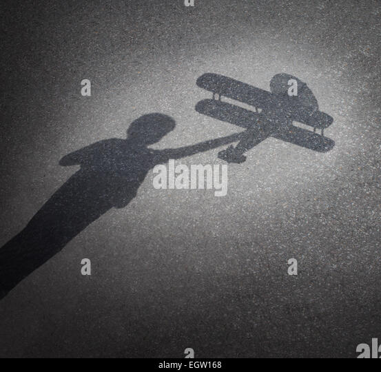 Childhood aspirations concept as a cast shadow on pavement of a child playing with a toy plane as a symbol for dreaming - Stock Image