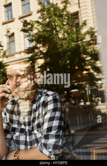 Sweden, Man sitting, talking on phone - Stock Image