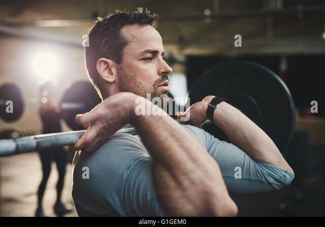 Fit young man lifting barbells looking focused, working out in a gym with other people - Stock Image