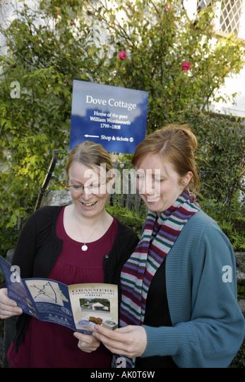 England UK Grasmere The Wordsworth Trust William Wordsworth poet Dove Cottage women read leaflet brochure - Stock Image