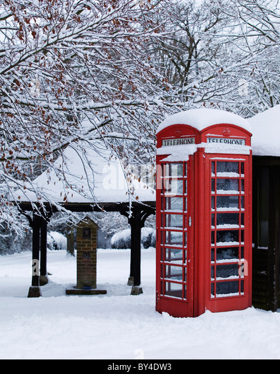 Red traditional telephone box with snow on a English village green - Stock Image