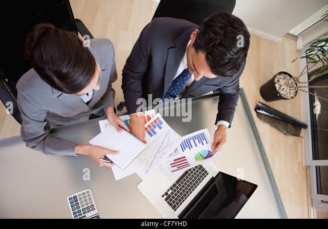 Focused sales persons studying statistics - Stock Image