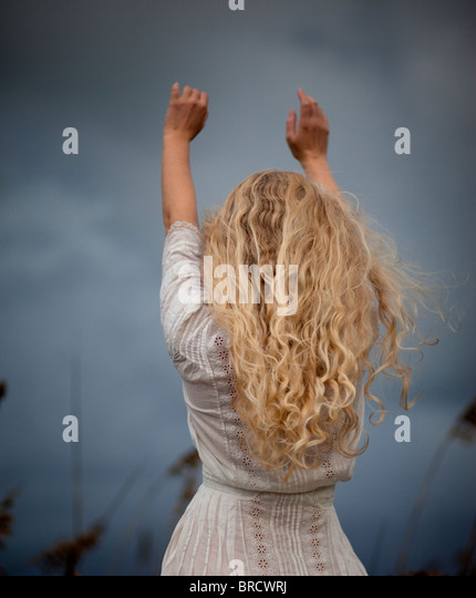 Back of Blond girl in white vintage dress - Stock Image