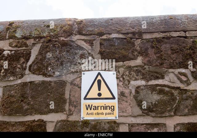 Warning anti climb sign on a brick wall - Stock Image