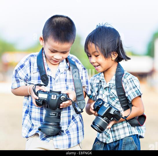 India, New Delhi, Boys holding cameras - Stock Image