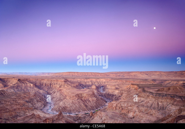 Full moon setting over the Fish River Canyon in southern Namibia at dawn. - Stock Image