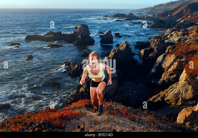 Fit mature woman exercises outdoors along Big Sur coastline and Pacific Ocean, California, USA. - Stock-Bilder
