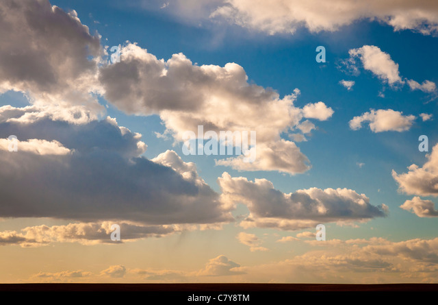 Cumulus clouds in sky over wheat field in eastern Washington. - Stock Image