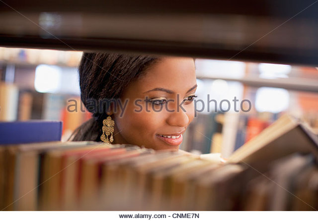 Smiling girl examining book in library - Stock Image