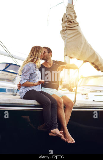 Sweet Young Couple Kissing at the Yacht Deck During Sunset Time. - Stock Image