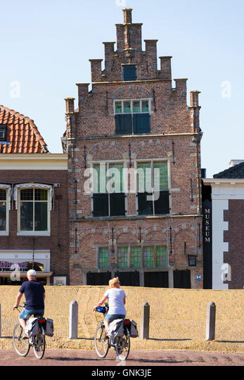 Cyclists and traditional architecture lopsided ancient building of theTown Hall Museum, Edam, The Netherlands - Stock Image
