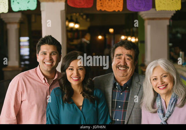 Portrait of smiling couples in restaurant - Stock Image