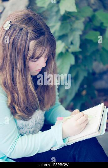 Portrait of teenage girl (13-15) writing - Stock Image