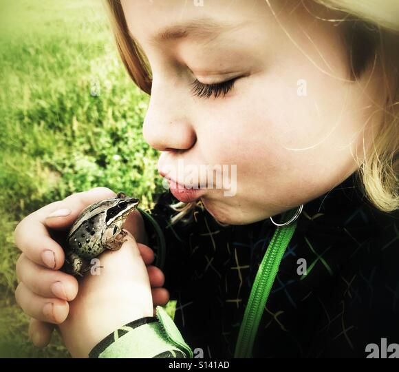 A girl purses her lips to kiss a frog. - Stock Image