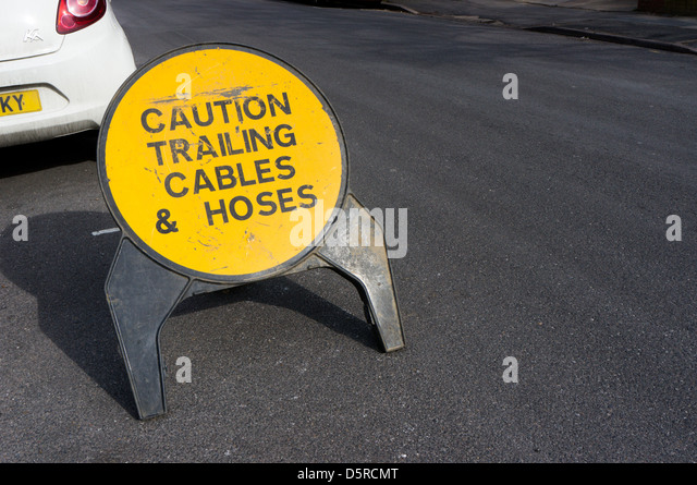 A sign warns of trailing cables and hoses before an area of road works. - Stock Image