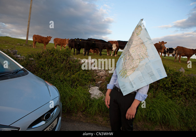 Businessman standing by field and covered in a road map - Stock Image